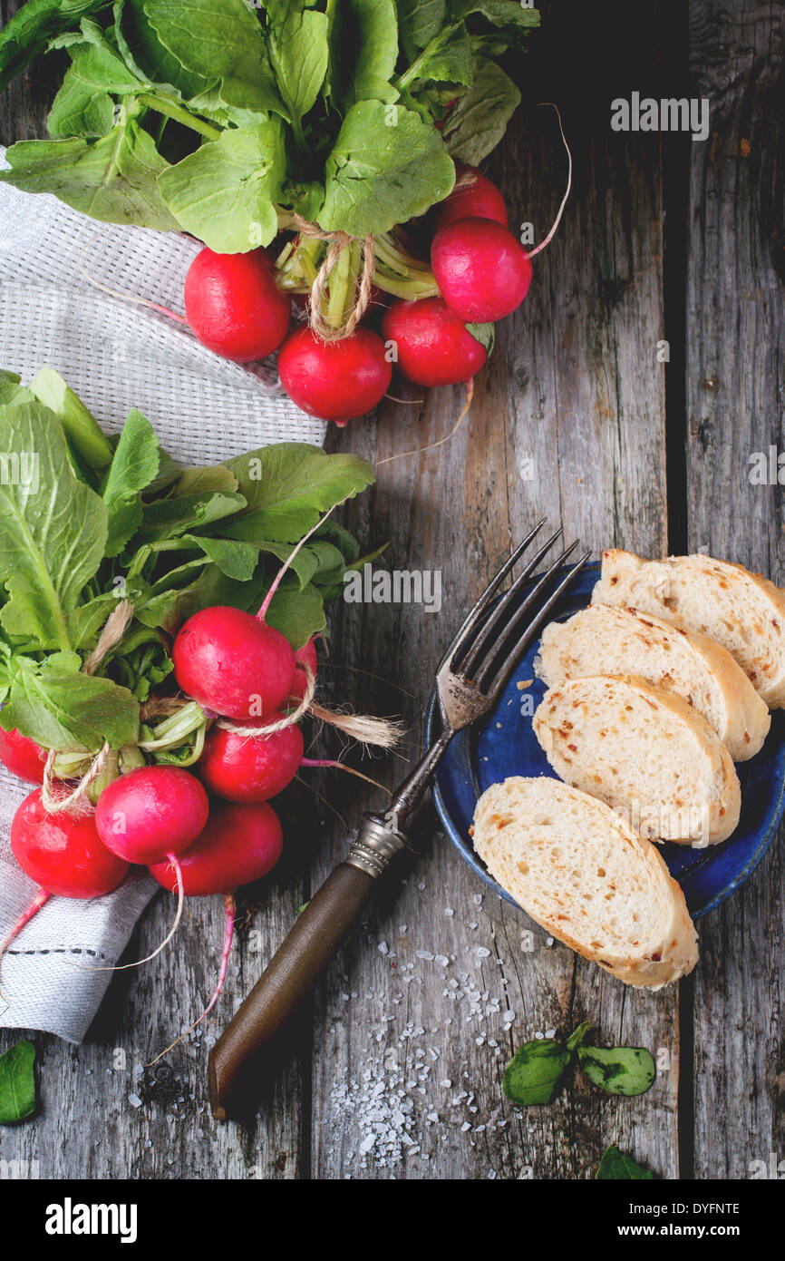 Frisches nass Radieschen mit Vintage Gabel, Meersalz und Brot über alten Holztisch. Ansicht von oben Stockfoto
