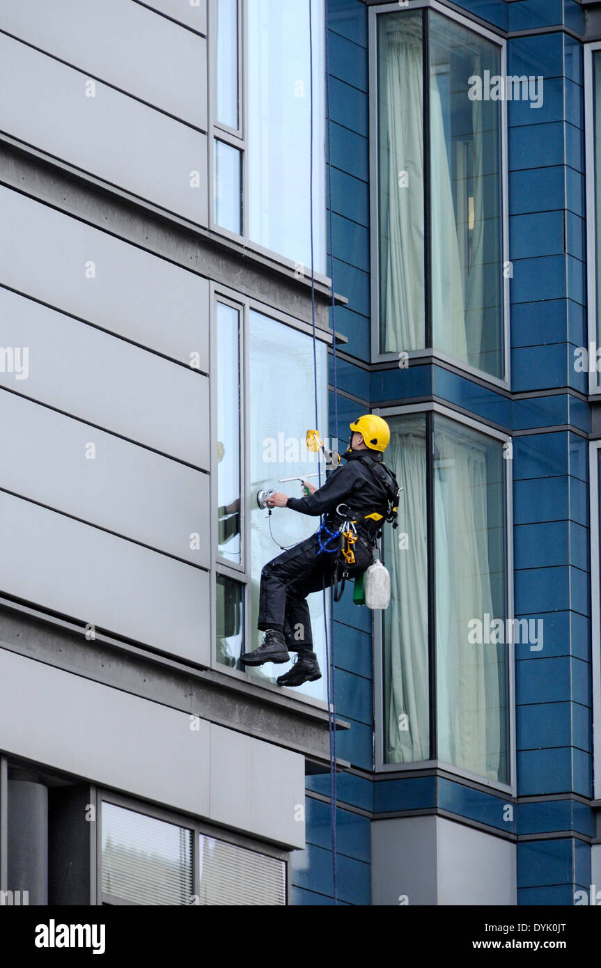Fenster-Reiniger mit industriellen Seiltechnik Zugang bei der Arbeit an einem Bürogebäude, London Road, Manchester, England, UK Stockbild