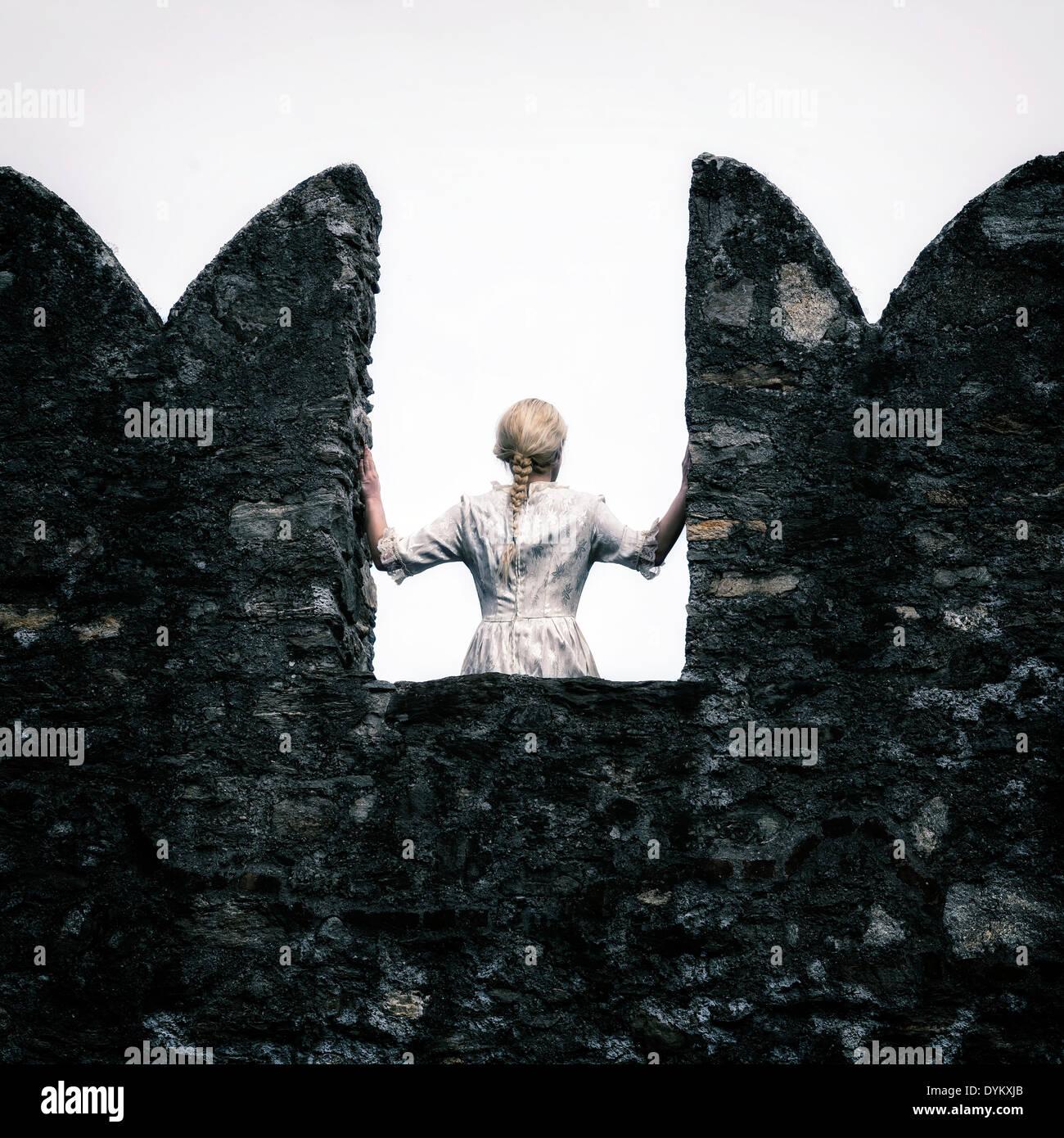 eine Dame mit einem weißen Periode Kleid steht auf einem Wehrgang Stockbild
