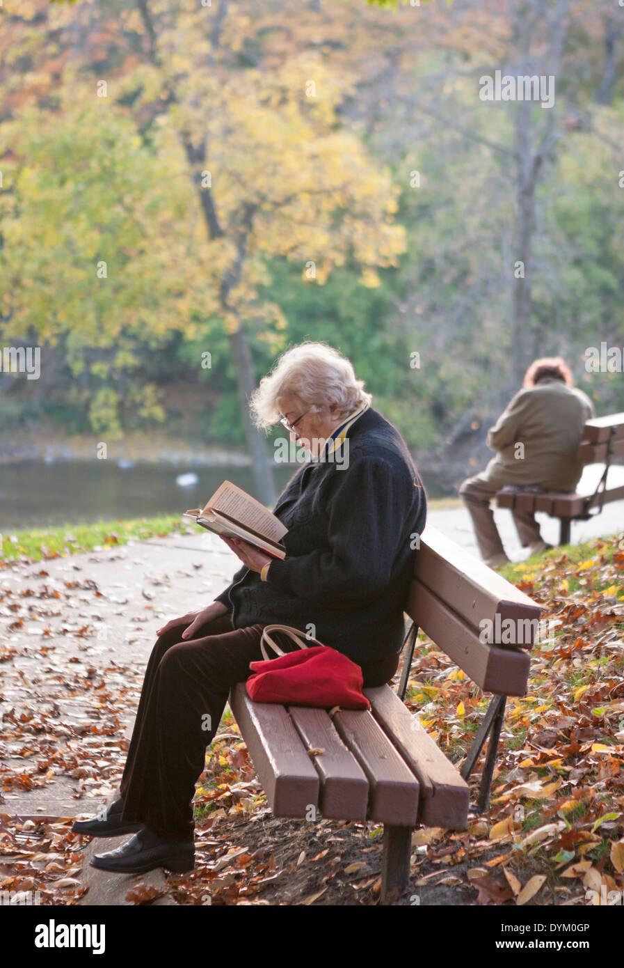 Zwei Frauen sitzen auf Bänken in einem Park. Stockbild