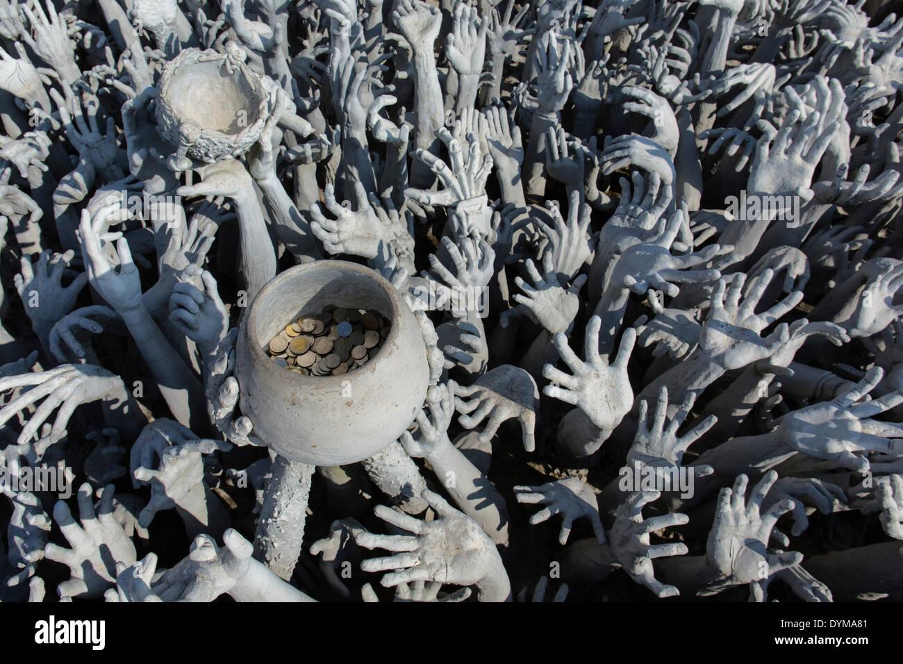 Darstellung der Hölle, Hände bittet um Hilfe und eine Bettelschale am Wat Rong Khun, Brücke zum Eingang des weißen Tempels, von Stockbild