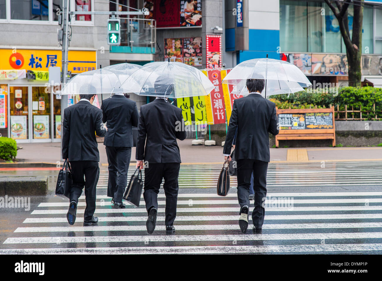 Erwachsene männliche japanische Arbeitnehmer gut gekleidet mit Sonnenschirmen, überqueren die Straße, Shinjuku, Tokyo, Japan Stockbild
