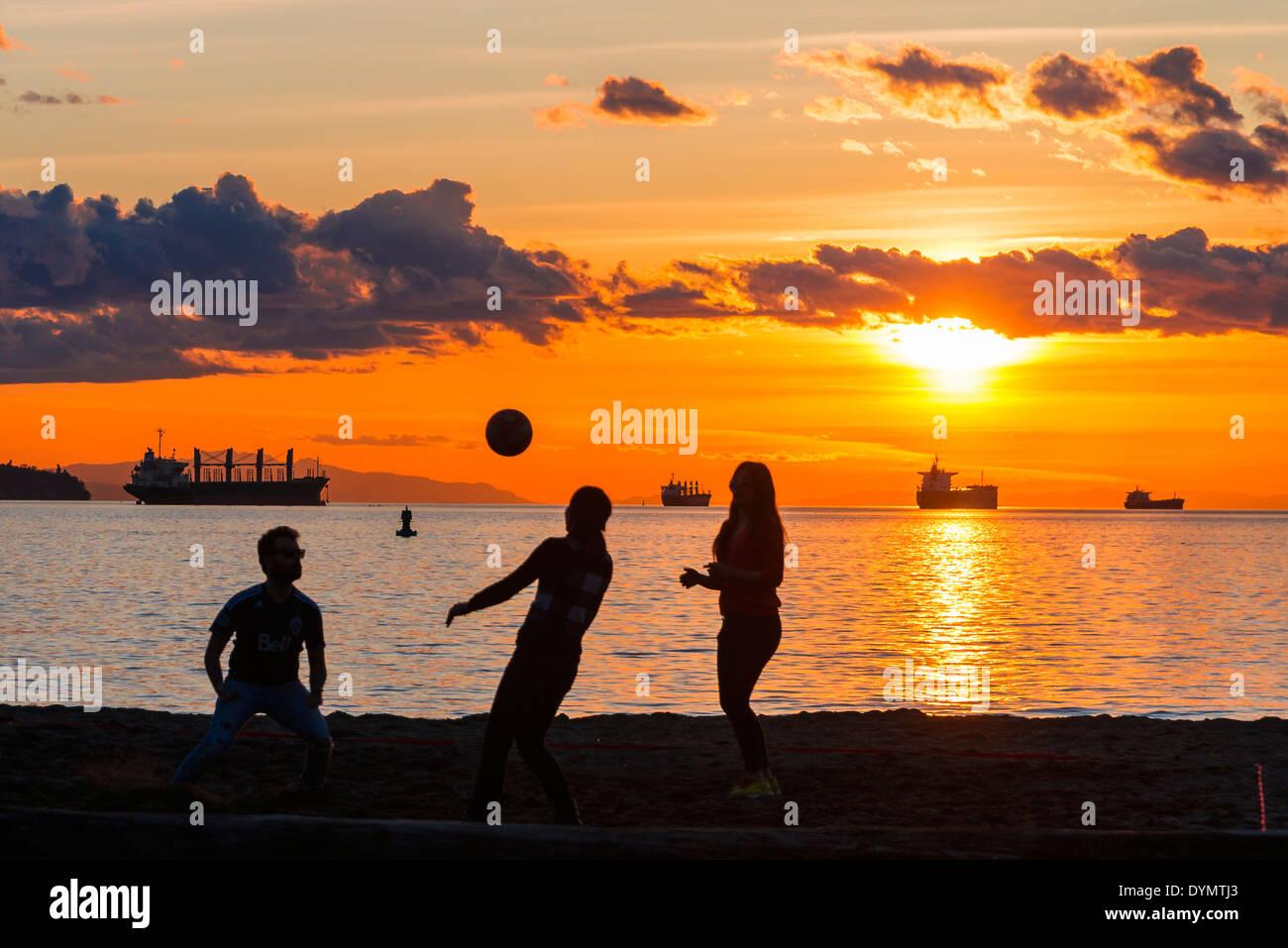 Eine Partie Beach-Volleyball bei Sonnenuntergang, Englisch Bay Beach, Vancouver, Britisch-Kolumbien, Kanada Stockbild