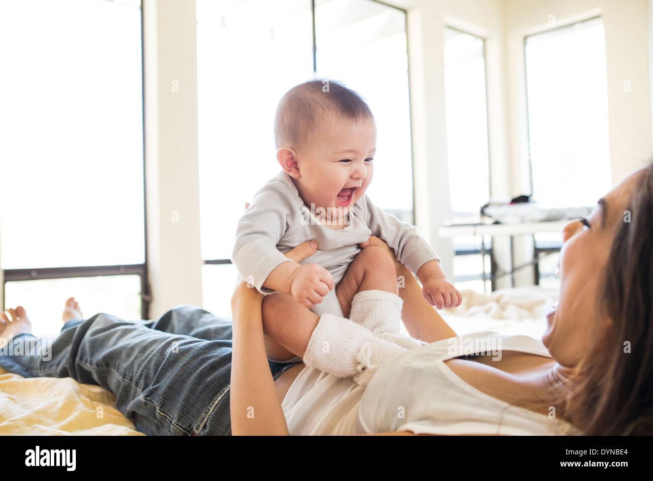 Mutter mit Babymädchen im Bett spielen Stockfoto
