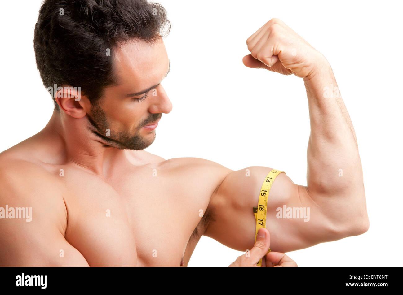 Fit Mann misst seine Bizeps mit einem gelben Band, isoliert in weiß Stockbild