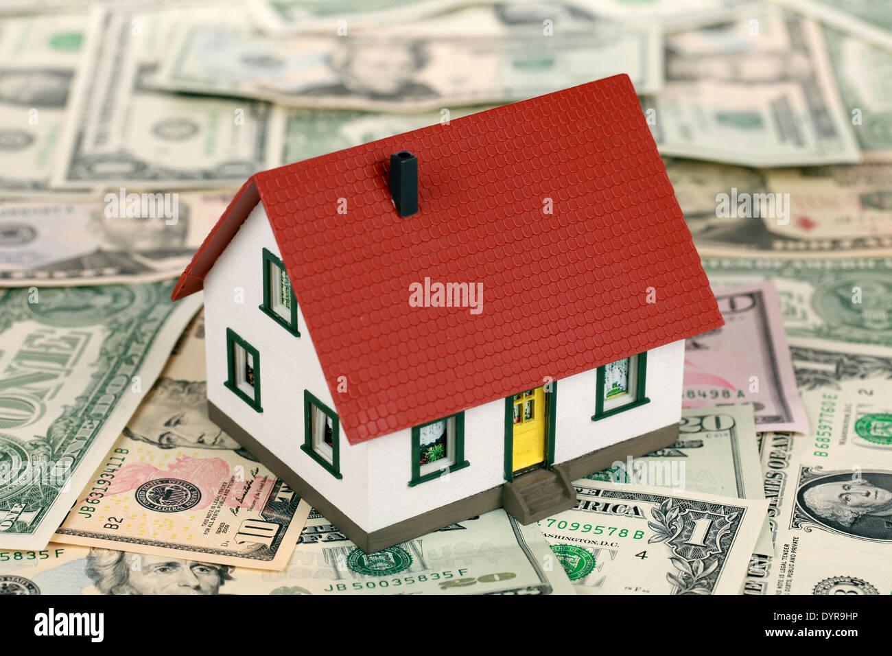 Symbol für Immobilienfinanzierungen mit einem Haus auf Dollarnoten Stockbild