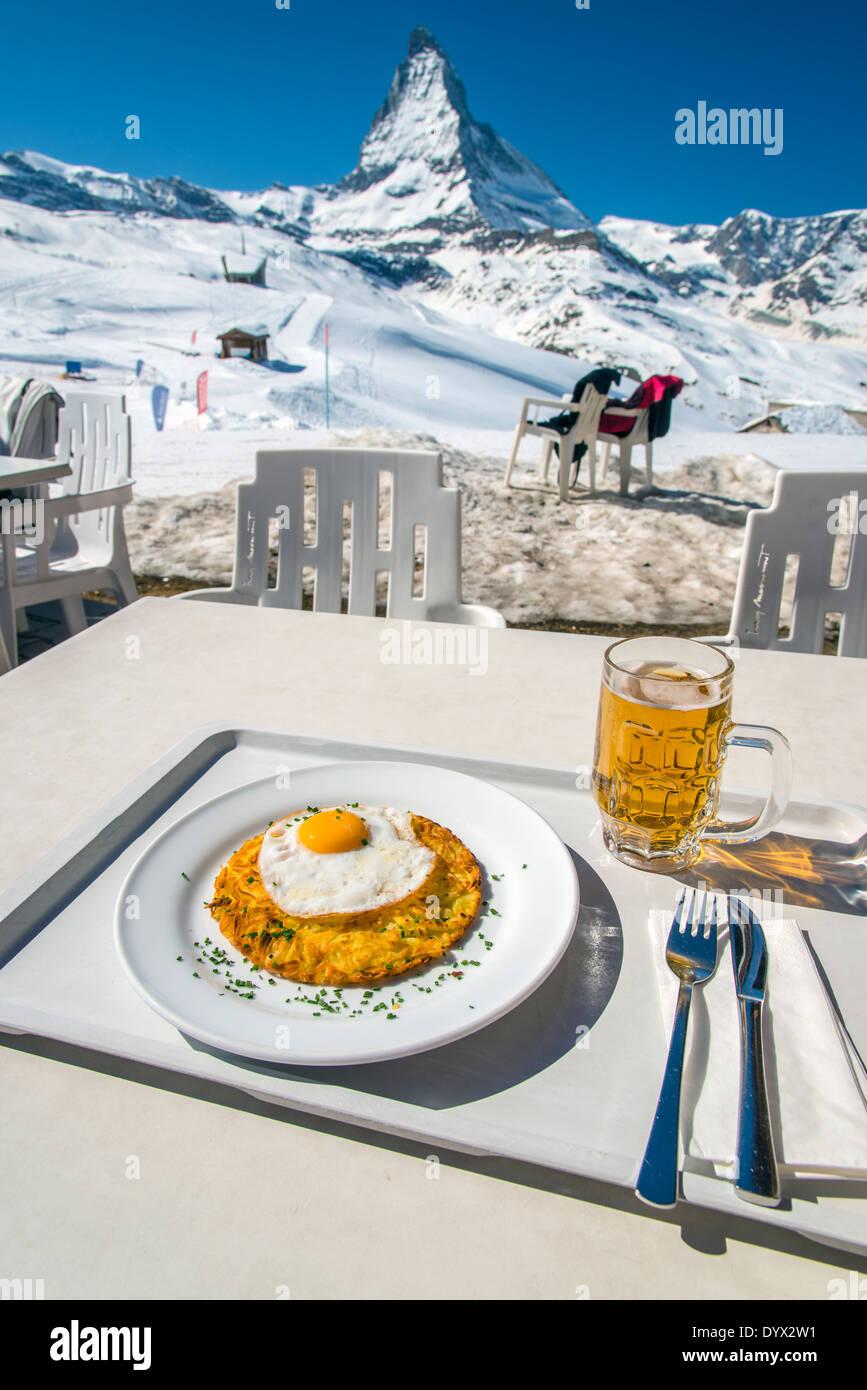Rösti mit Spiegelei, ein Schweizer Gericht mit Matterhorn im Hintergrund, Zermatt, Wallis oder Wallis, Schweiz Stockbild