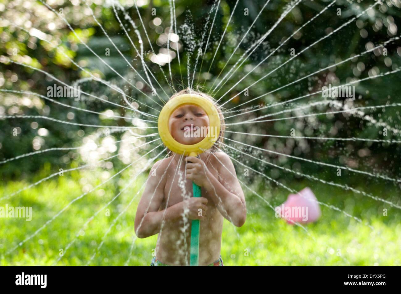 Ein Junge spielt mit einem Sprinkler im Garten. Stockbild