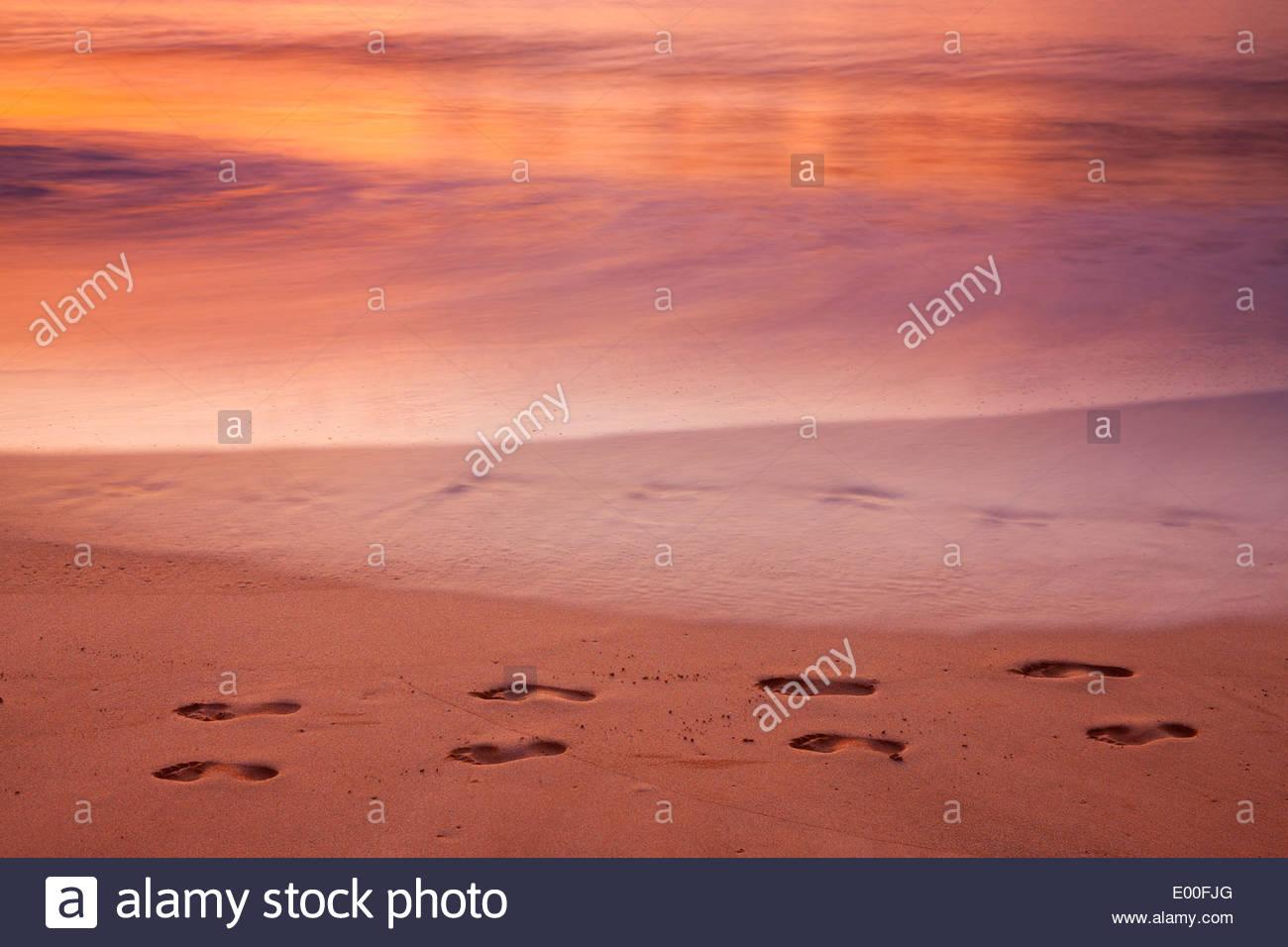 Wellen des Pazifischen Ozeans löschen allmählich Fußabdrücke hinterlassen Makena Beach auf der Insel Maui, Hawaii als die Sonne untergeht. Stockbild