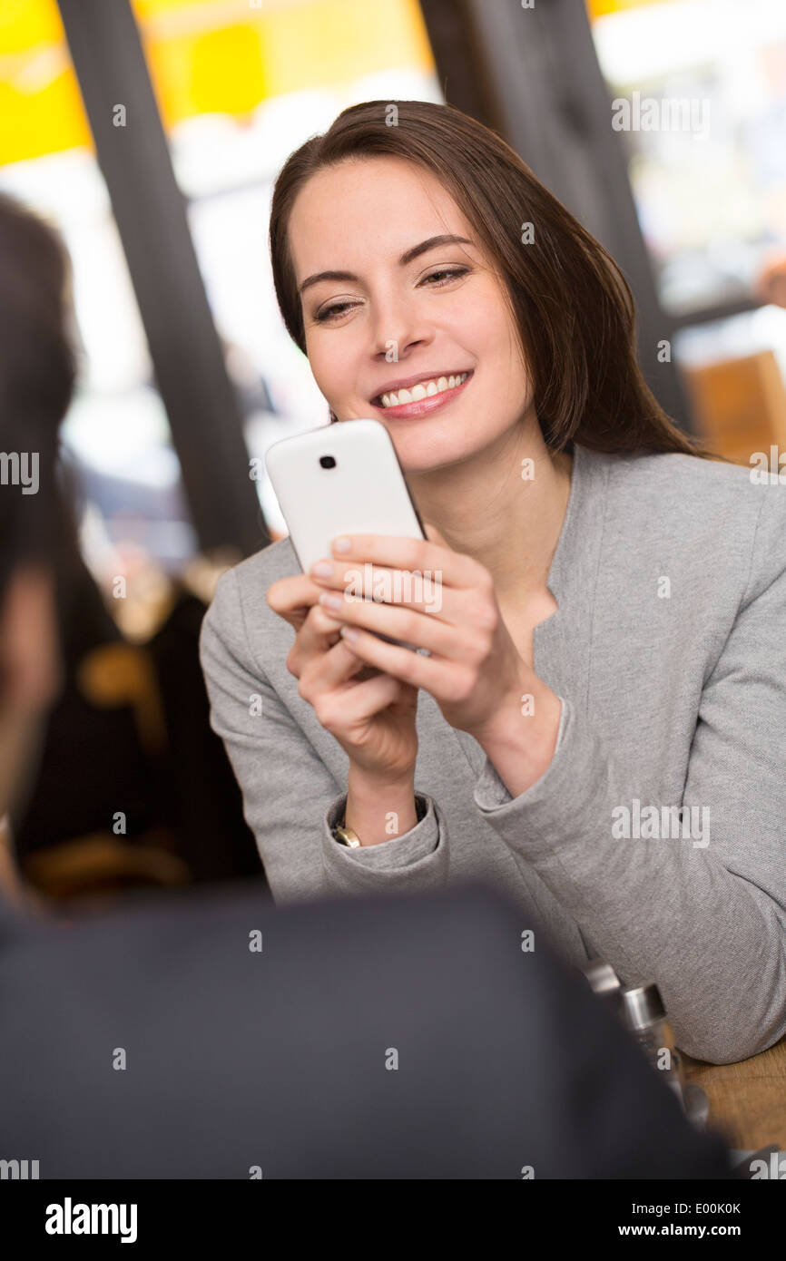 Weiblich männlich fröhlich Smartphone Abendessen Bar Foto Stockbild