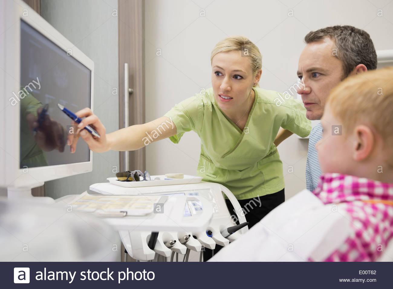 Zahnarzthelferin, die Überprüfung der Röntgenstrahlen mit Patienten Stockbild