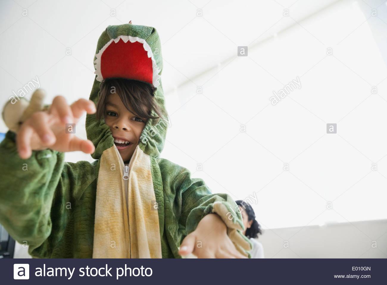 Verspielte junge im Drachenkostüm Stockbild