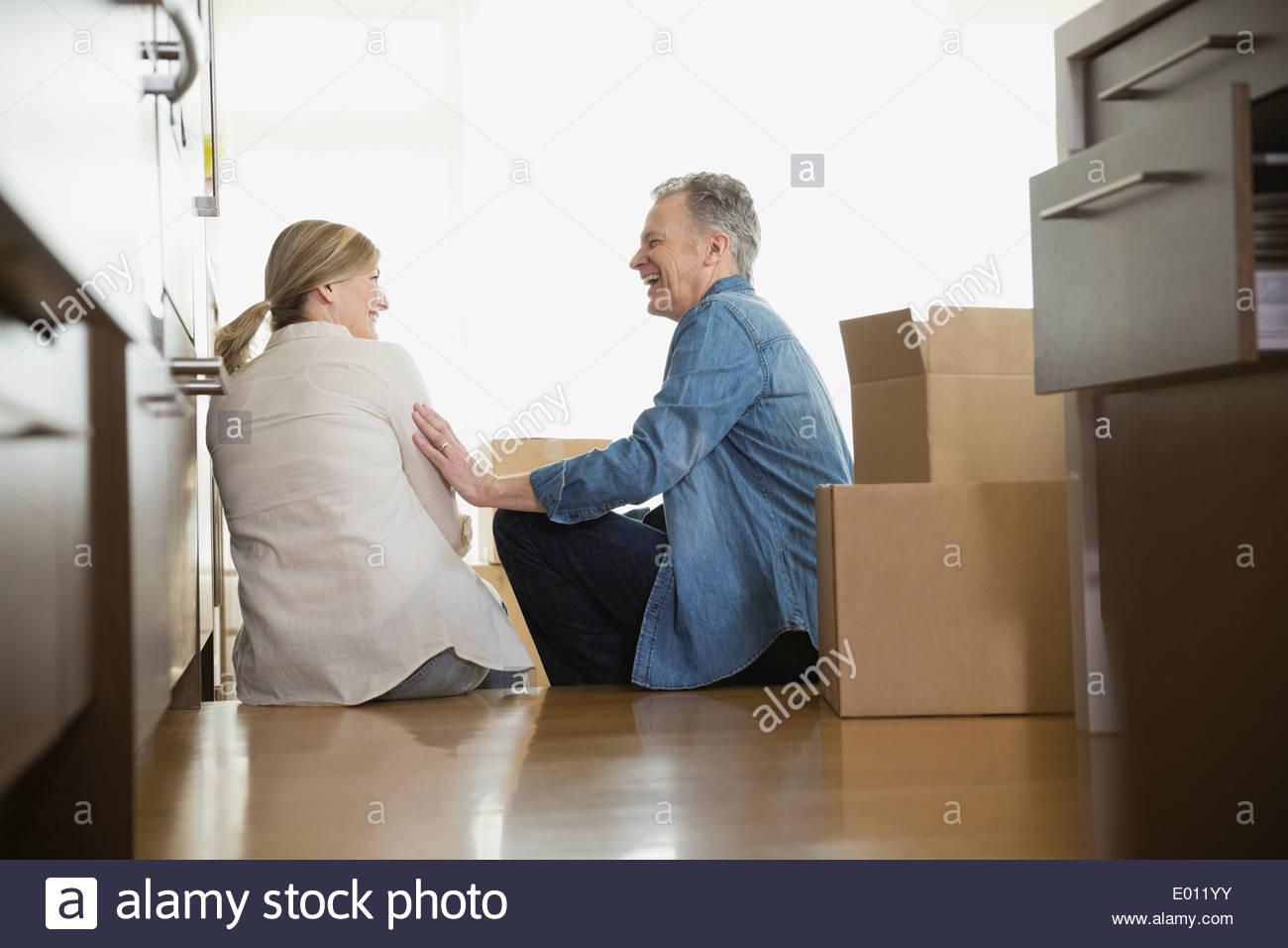 Paar lachend am Boden in der Nähe von Umzugskartons Stockbild