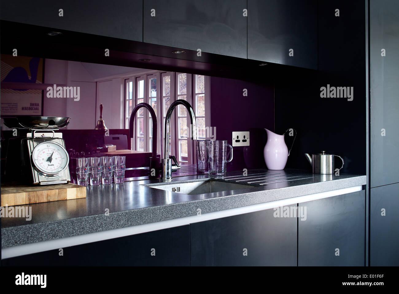 Küche-Detail, lila Glas-Spritzschutz hinter der Spüle Stockfoto ...