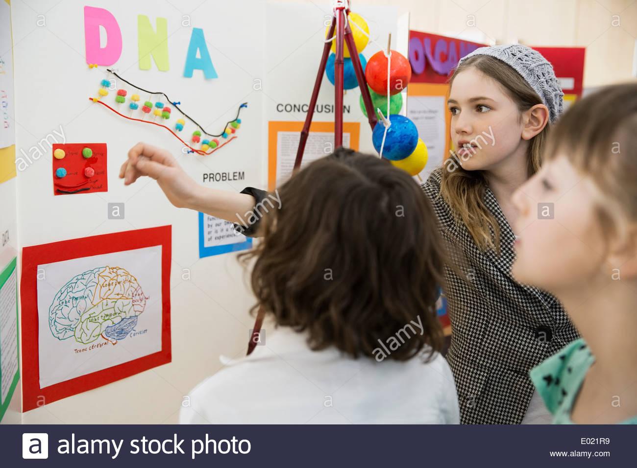 Schulmädchen, Mitschüler zu erklären, wissenschaftliches Projekt Stockbild