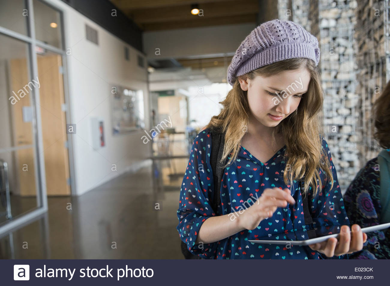 Schulmädchen mit digital-Tablette im Korridor Stockbild