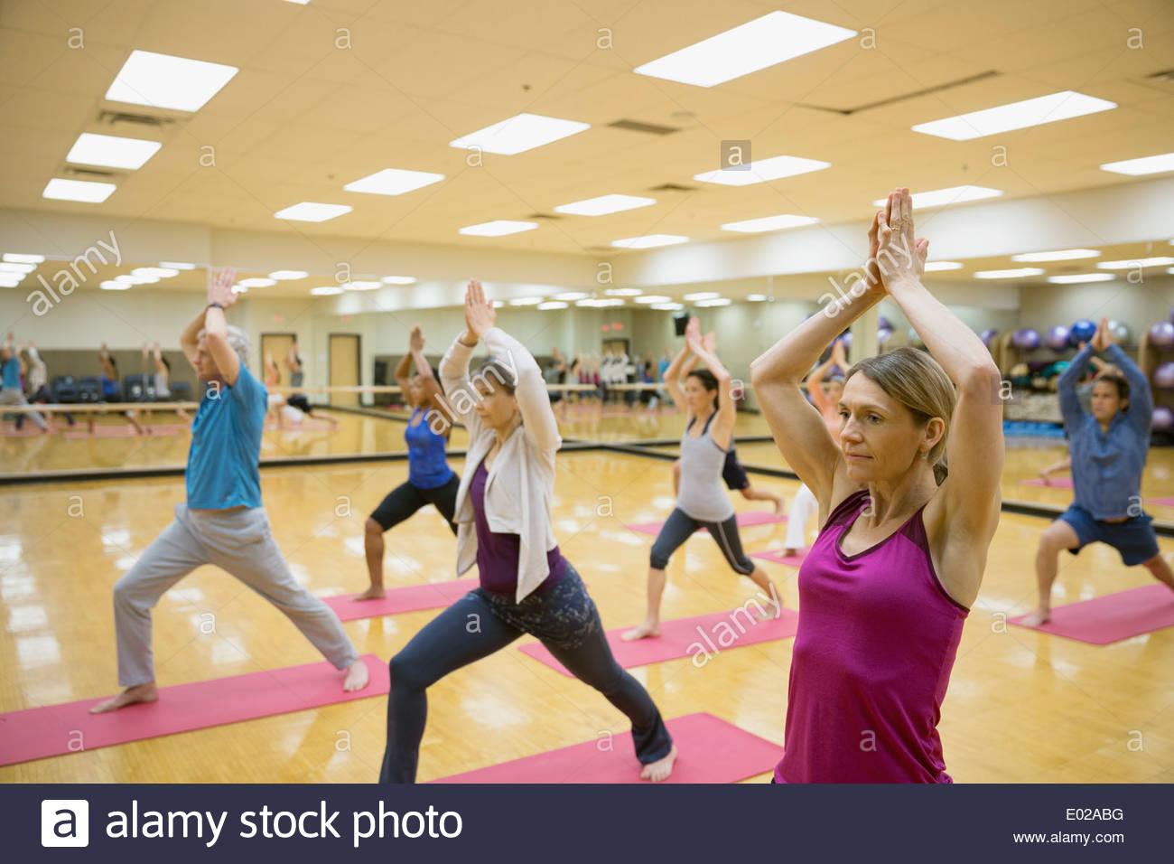 Gruppe praktizierender Halbmond Longe in Yoga-Kurs Stockbild