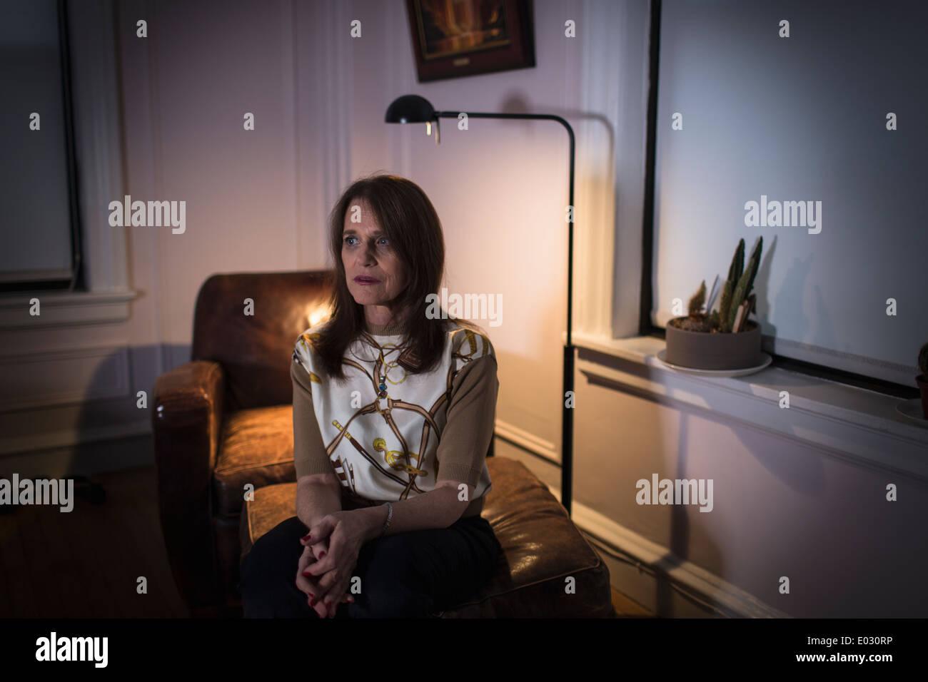Eine Frau mittleren Alters mit einem traurigen Ausdruck sitzen. Stockbild