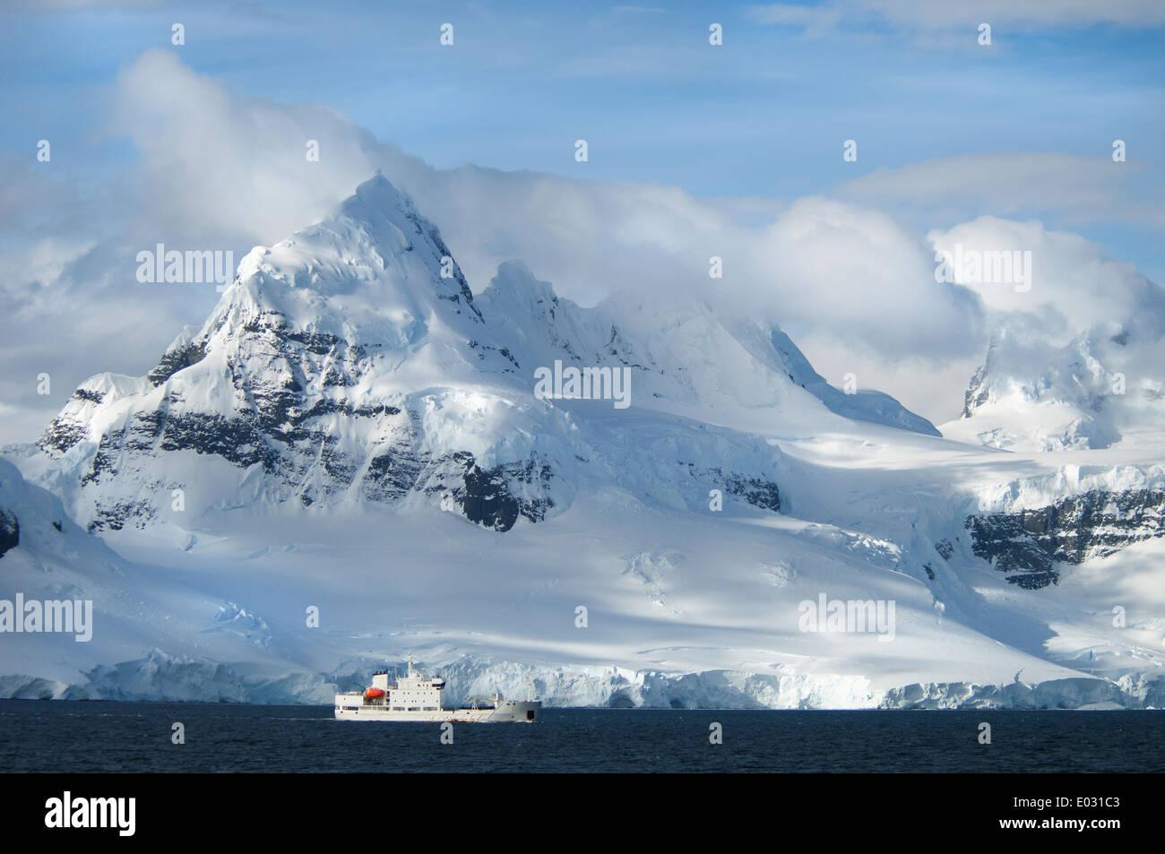 Ein Schiff unter der hoch aufragenden Form einer Bergkette. Stockbild
