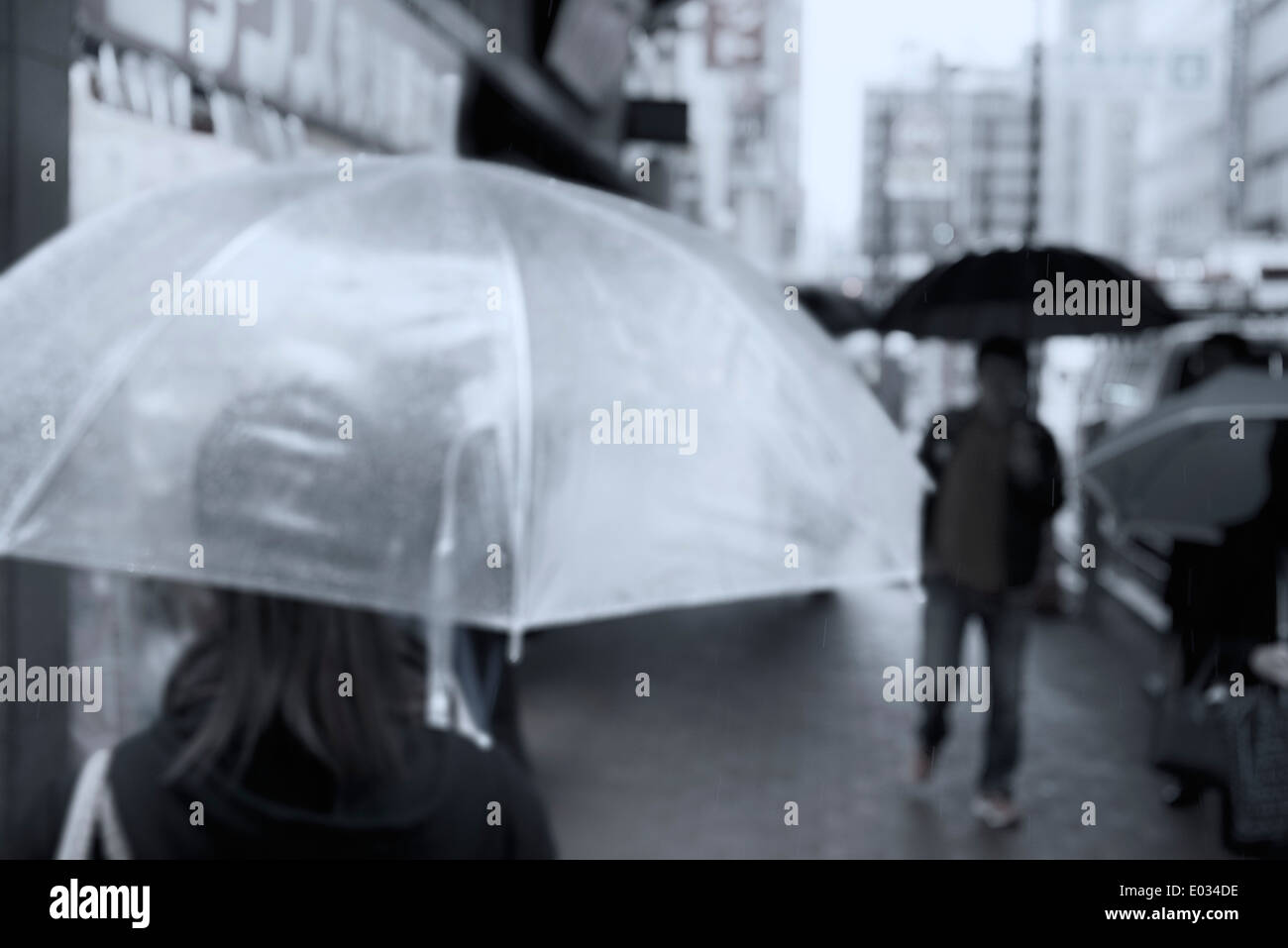 Aus Focus Foto von Menschen mit Regenschirmen, die Straßen von Tokio, Japan Stockbild