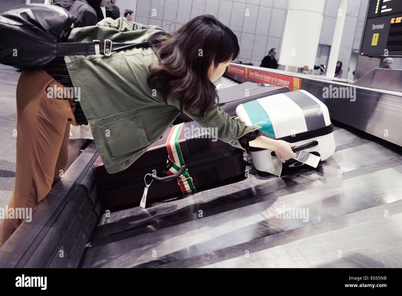 Frau, die Abholung der Koffer vom Flughafen Gepäck Förderer an Toronto Pearson internationaler Flughafen Gepäck Anspruch, Kanada Stockbild