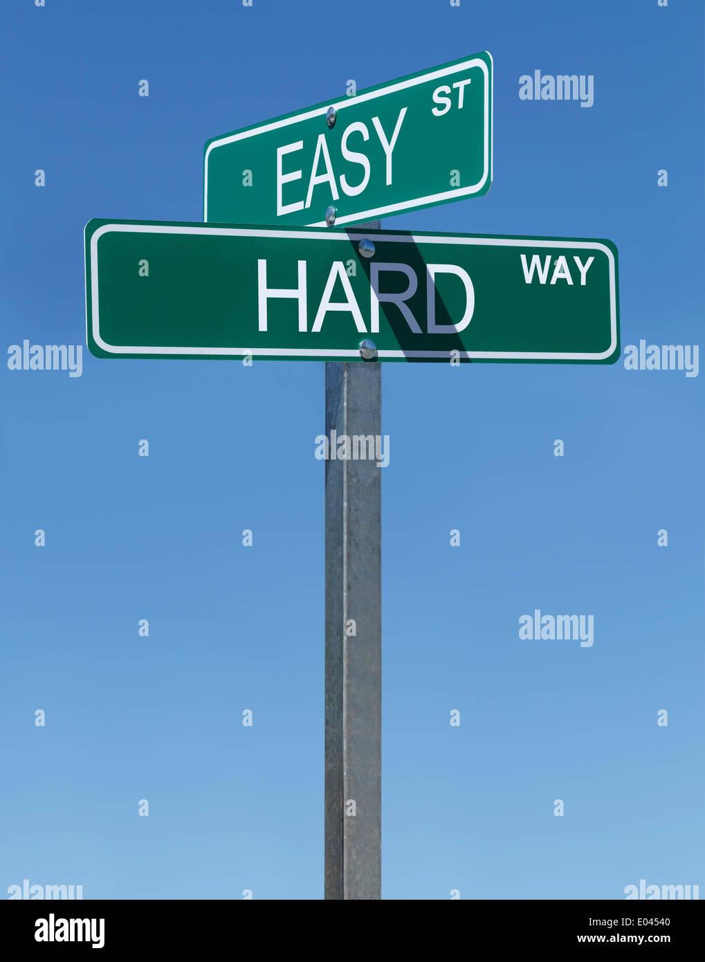 Zwei grüne Straße Zeichen Easy Street und harte Tour mit blauem Himmelshintergrund. Stockbild