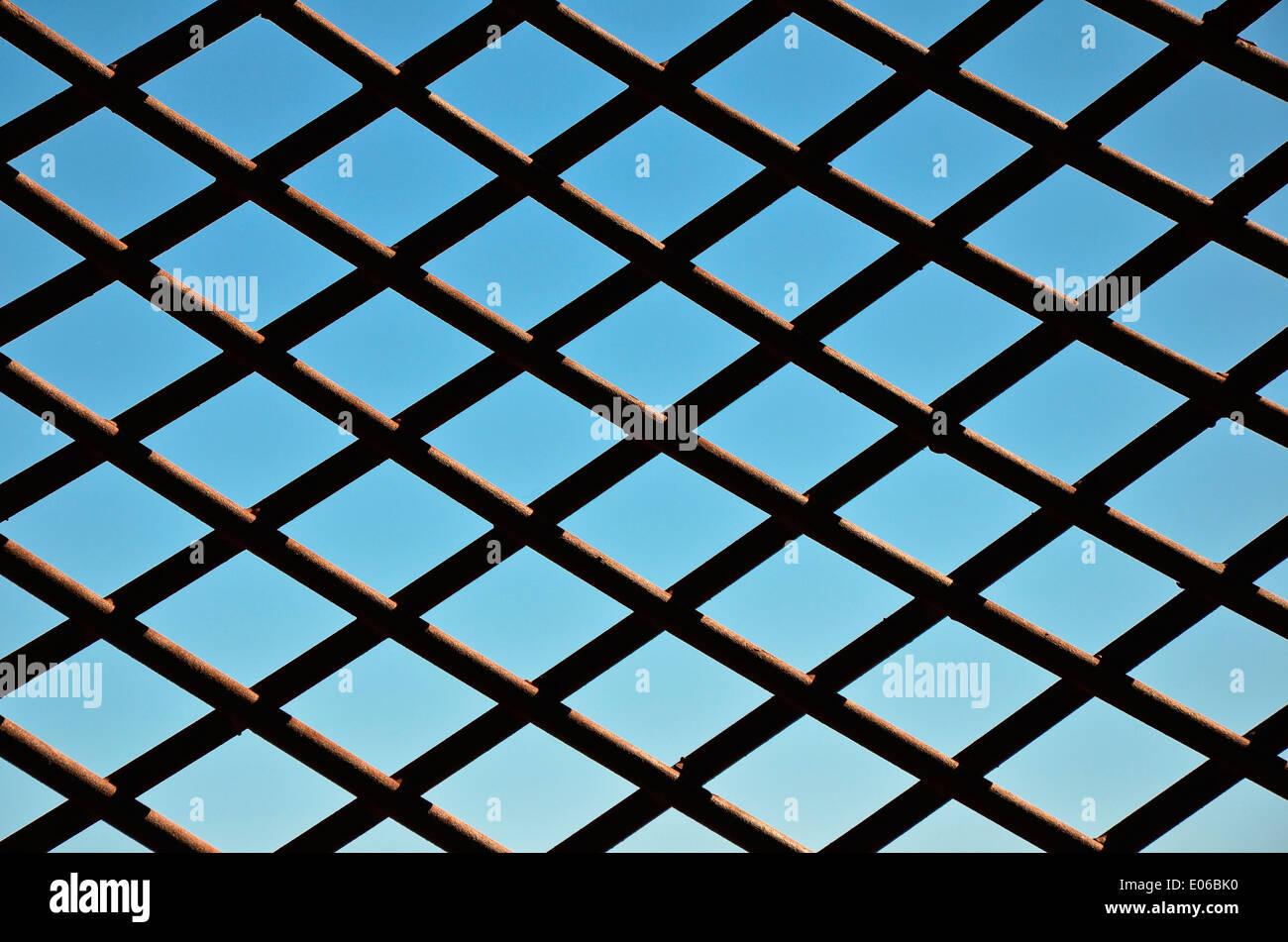 Maschendrahtzaun gegen blauen Himmel - Abschnitt von einem Maschendrahtzaun, hinter den blauen Himmel als ein Symbol für Gefangenschaft und Freiheit. Stockbild