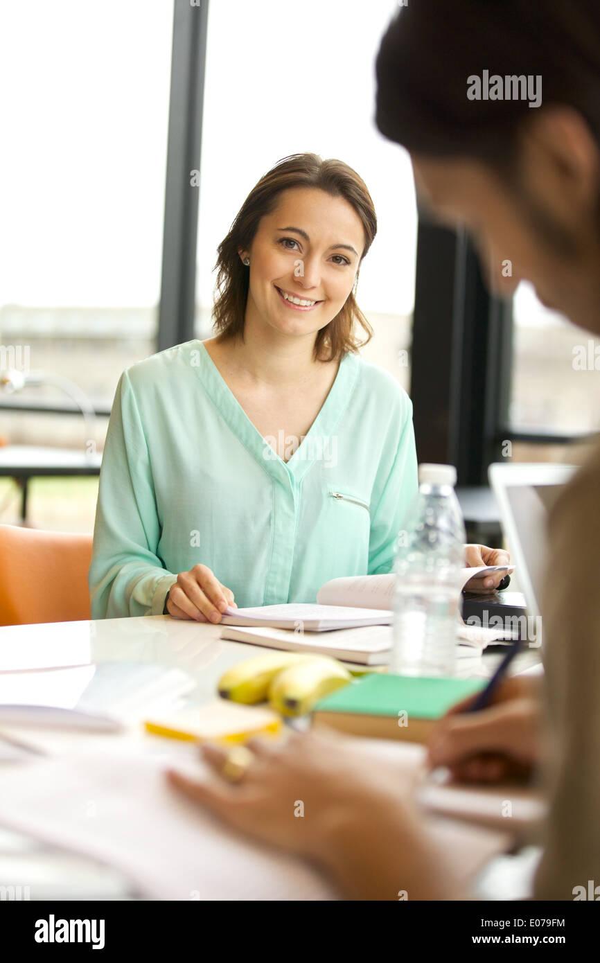 Glückliche junge kaukasischen Frau Blick auf die Kamera zu Lächeln. Studentin am Tisch mit Büchern Stockbild