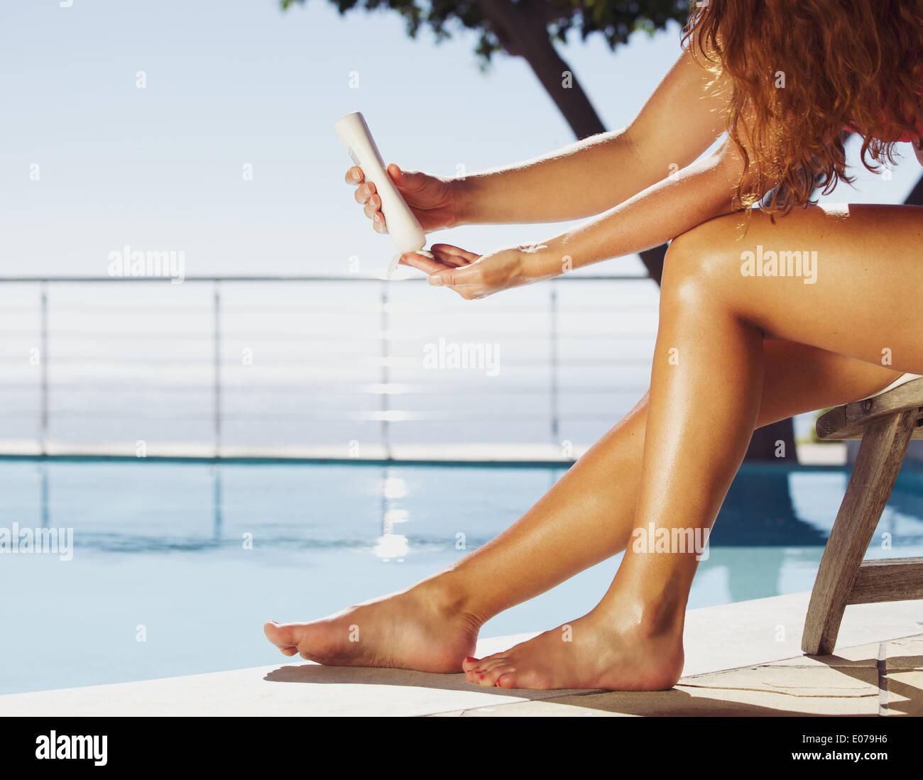 Frau sitzt auf Liegestuhl durch das Schwimmen pool Anwendung Sonnencreme auf ihre Beine. Weibliches Model Sonnenbaden am Pool. Stockbild