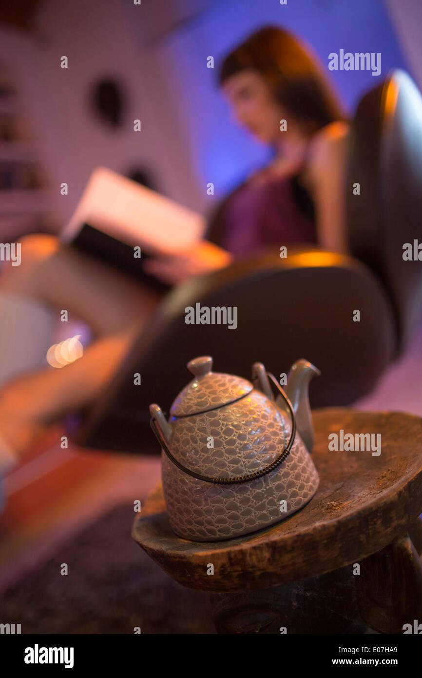 Junge Frau, ein Buch lesen, Teekanne im Vordergrund Stockbild