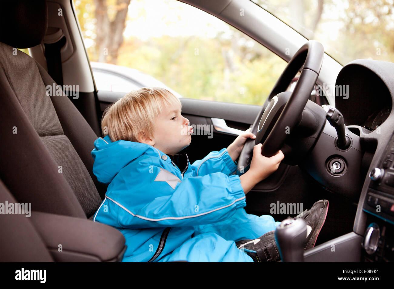 Voller Länge Seitenansicht eines jungen mit Auto Lenkrad Stockbild