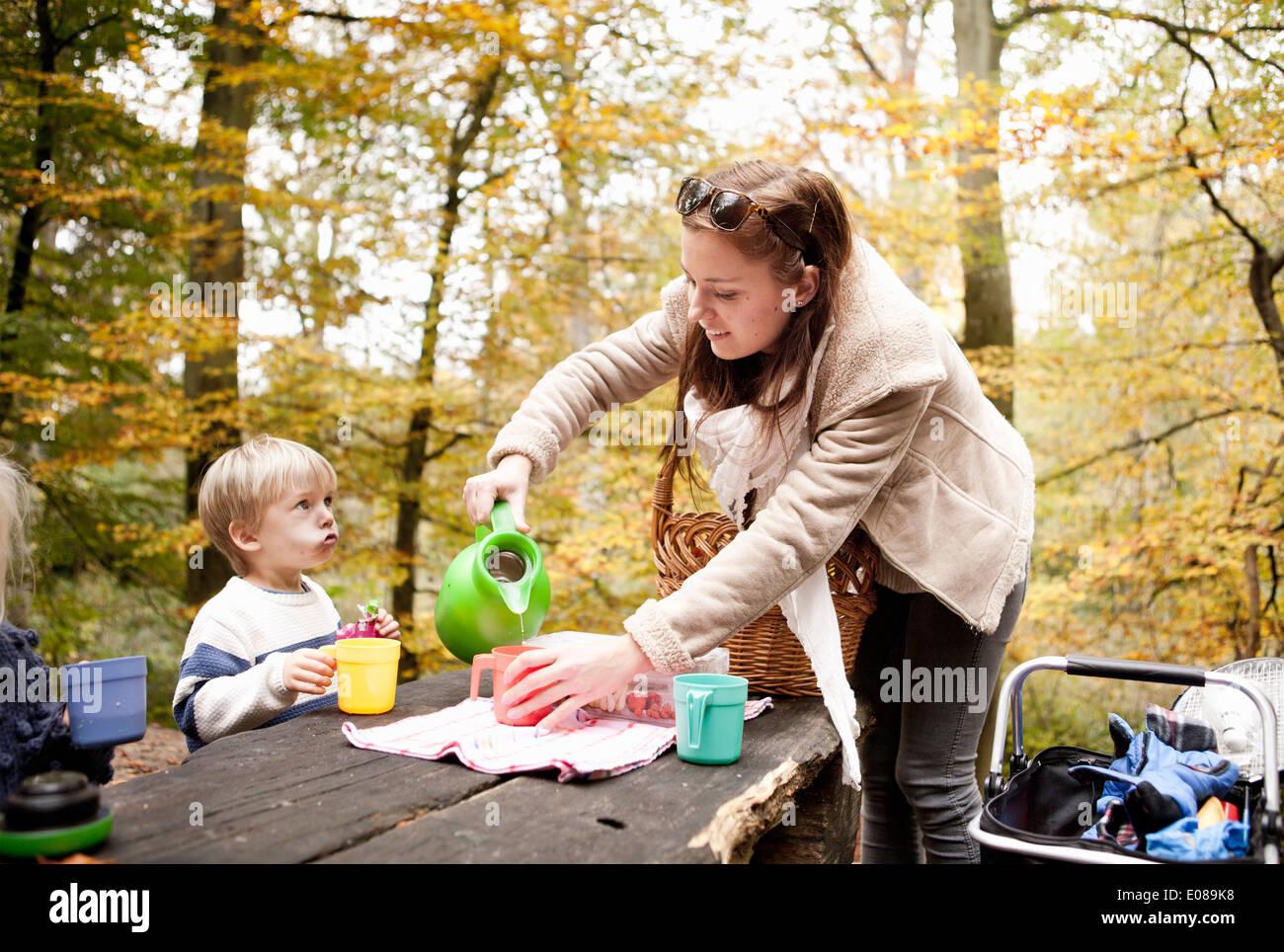 Mutter, Picknick im Wald trinken für Sohn herein Stockbild