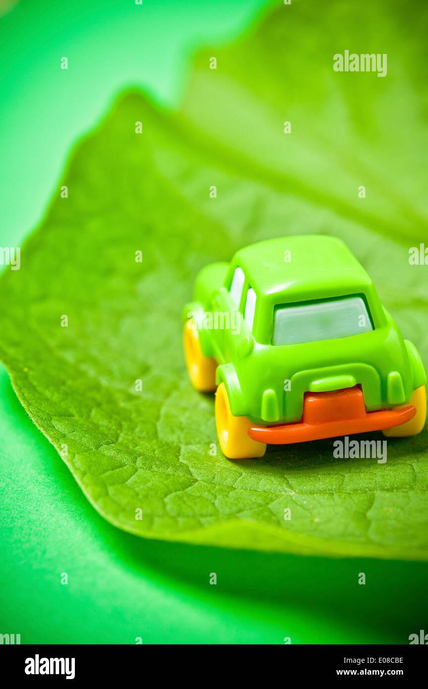 kleine grüne Spielzeugauto auf einem Blatt, Grün Auto Konzept Stockbild