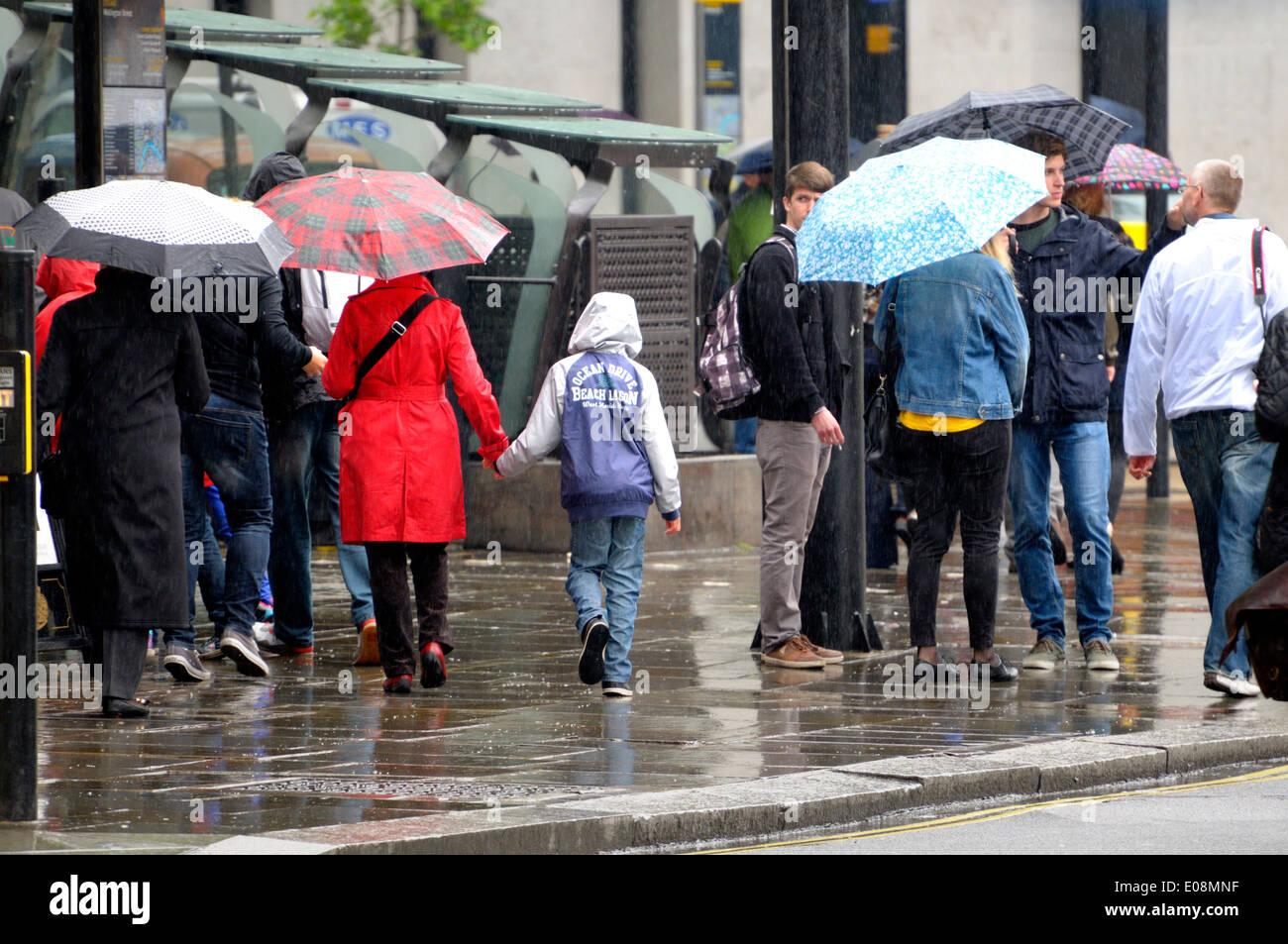 London, England, Vereinigtes Königreich. Menschen wandern in den Regen mit Sonnenschirmen Stockbild