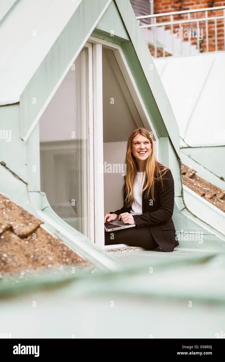 Glücklich Geschäftsfrau mit Laptop sitzen auf Bürofenster Stockbild