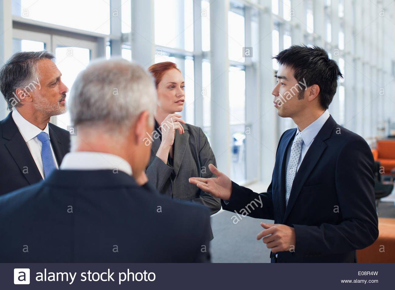 Geschäftsleute, die im Büro Lobby sprechen Stockbild