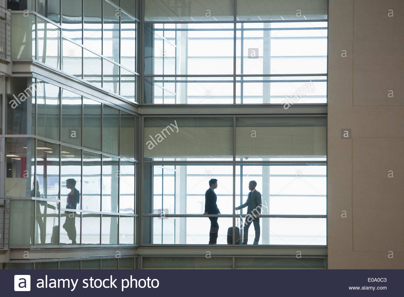 Geschäftsleute, die entlang der Flur im modernen Büro Stockbild