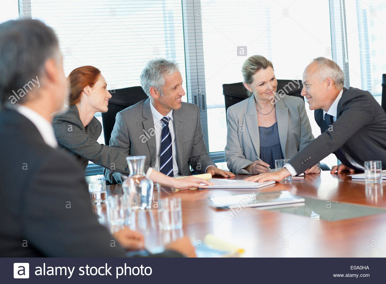 Lächelnde Geschäftsleute treffen am Tisch im Konferenzraum Stockbild