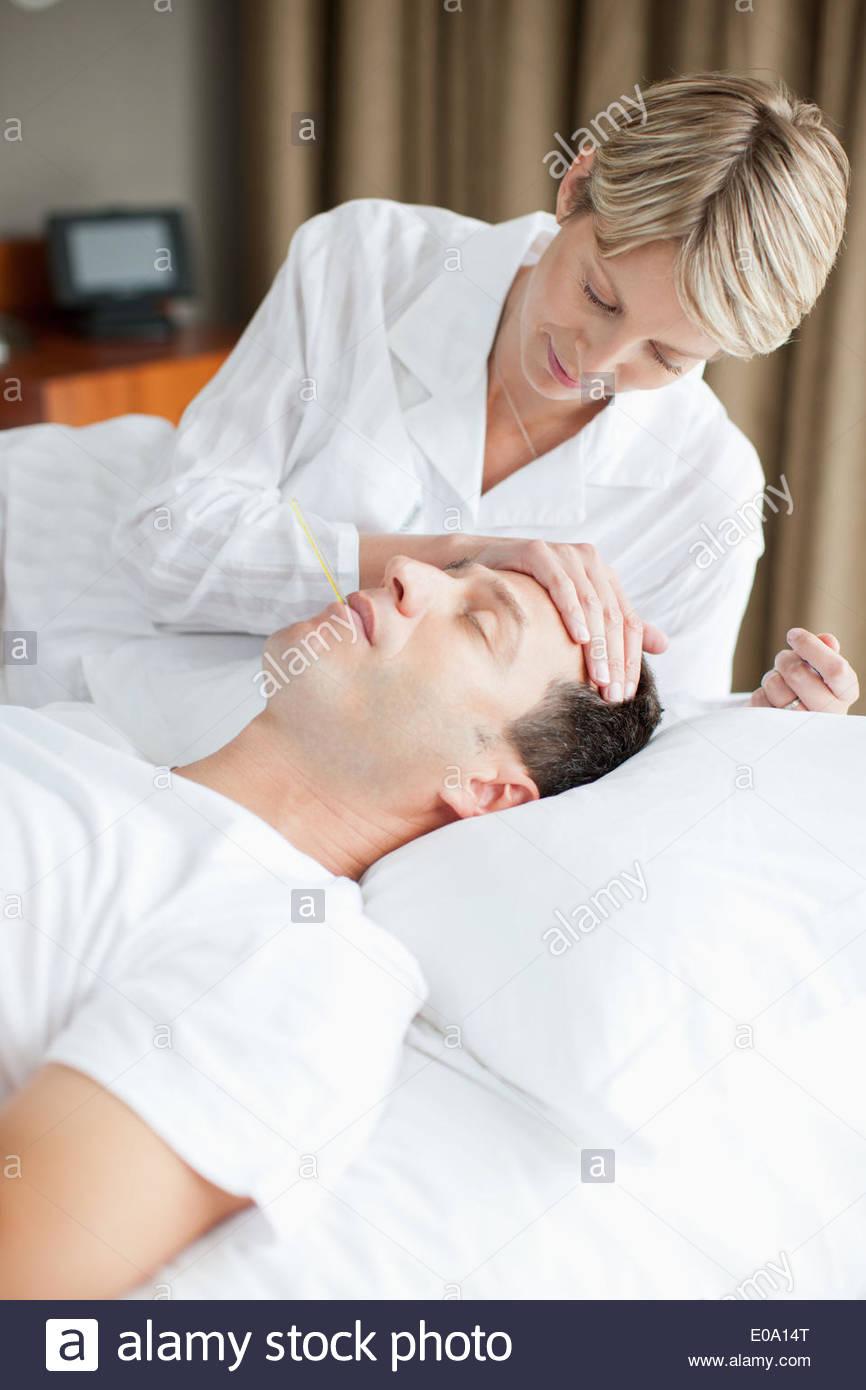 Frau nehmen HusbandTemperatur Stockbild