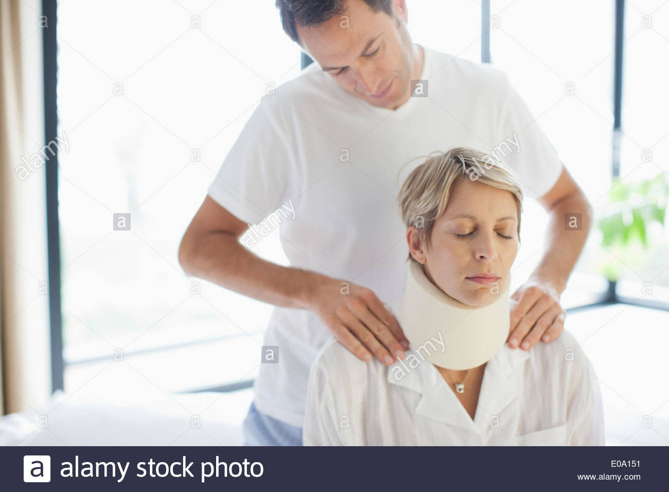 Mann Frau in Halskrause zu helfen Stockbild
