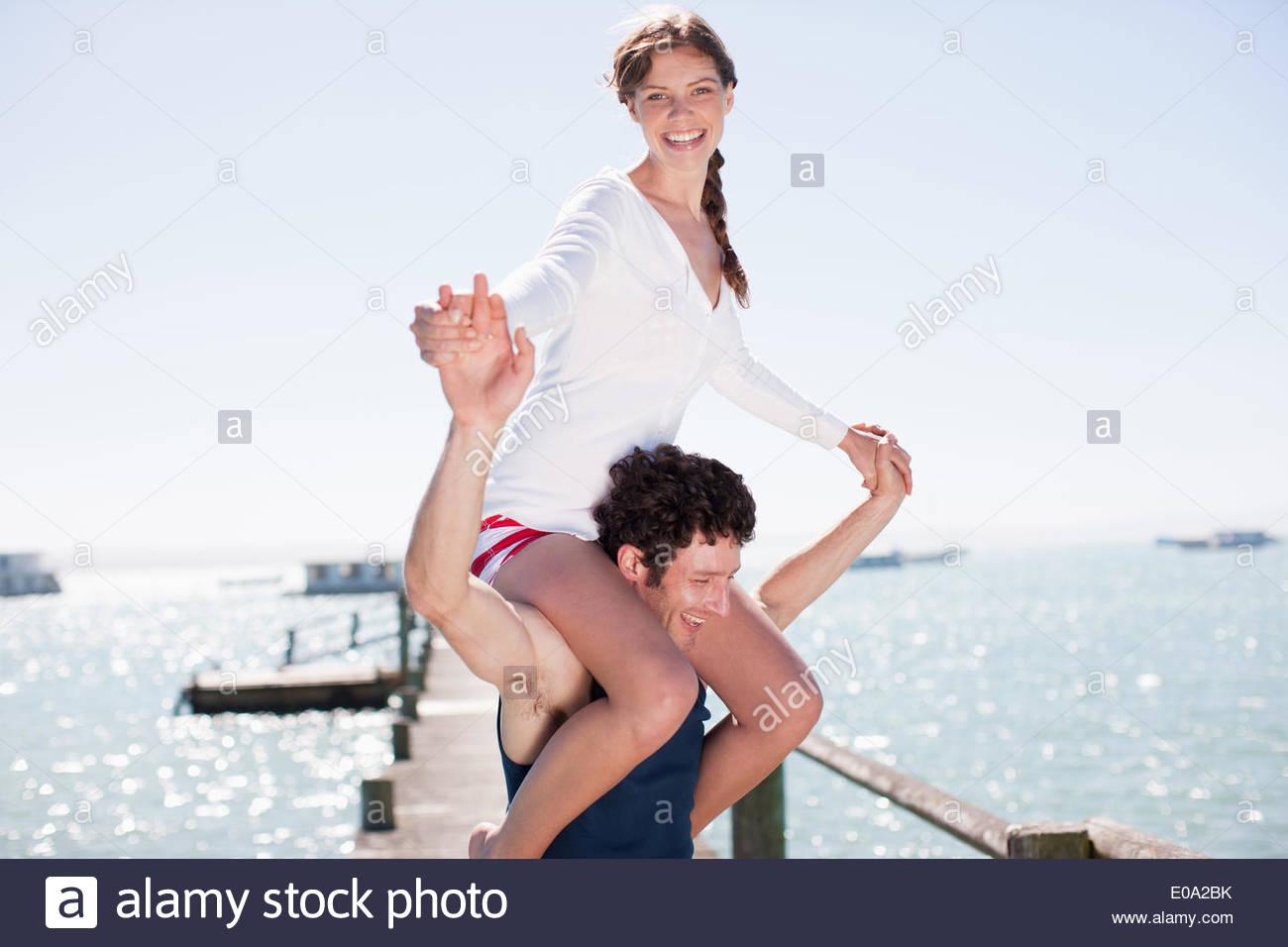 Mann trägt Frau auf Schultern auf Pier am Ozean Stockbild