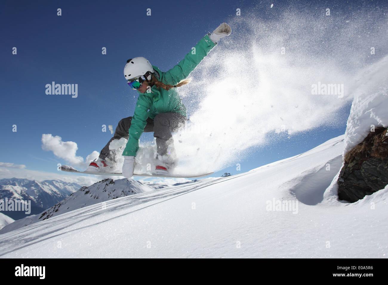 Junge Frau springt auf Snowboard, Mayrhofen, Tirol, Österreich Stockbild