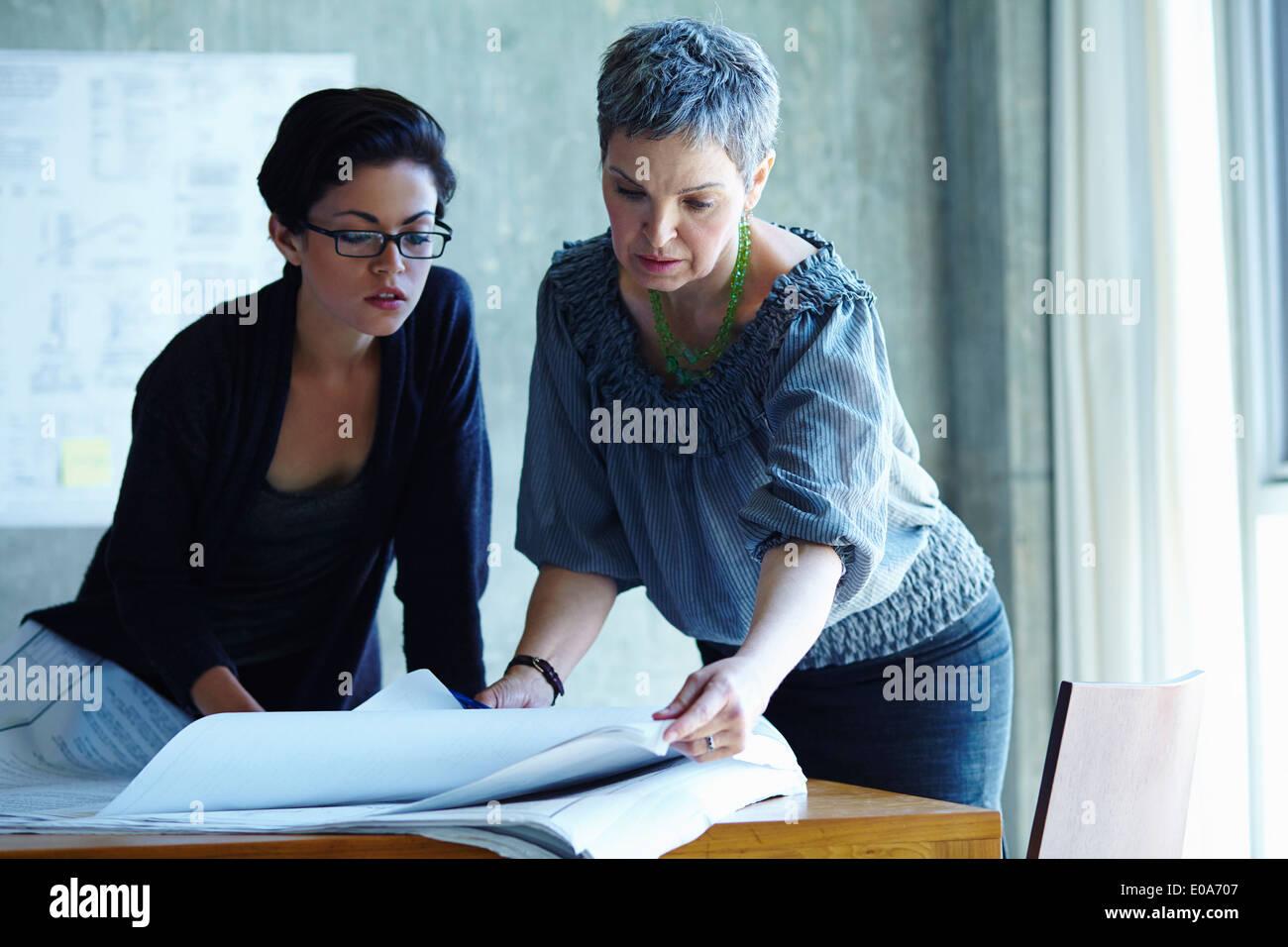 Zwei Geschäftsfrauen Überprüfung Blaupausen im Büro Stockbild