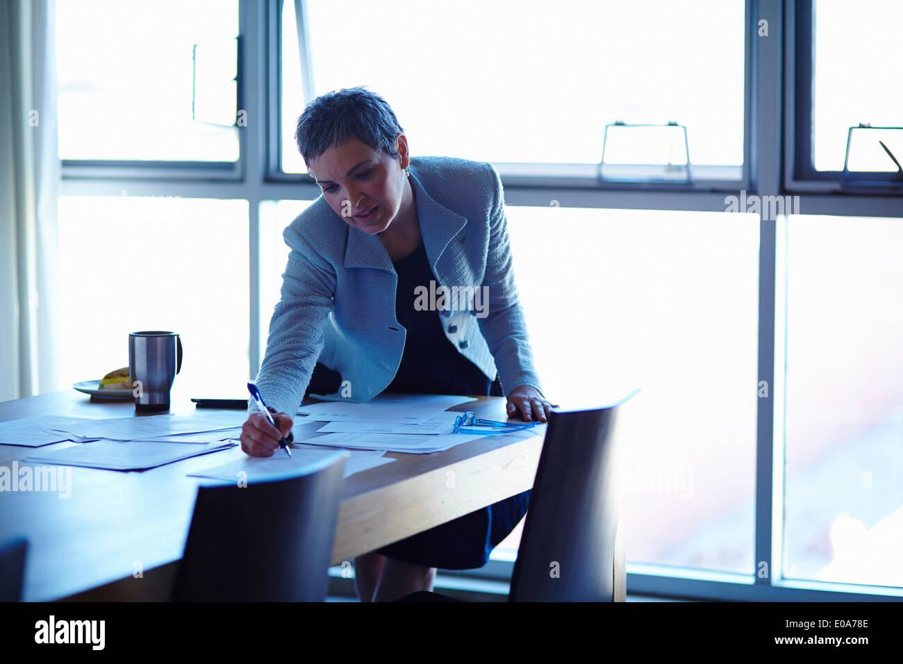 Reife Geschäftsfrau am Konferenztisch Prüfung Papiere Stockbild