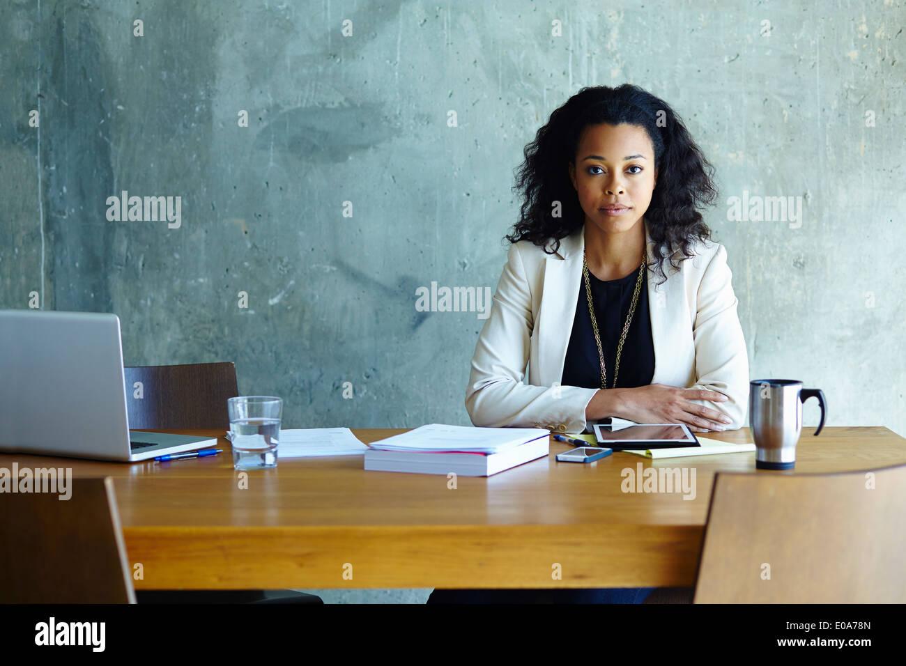 Porträt der jungen Unternehmerin am Konferenztisch Stockbild