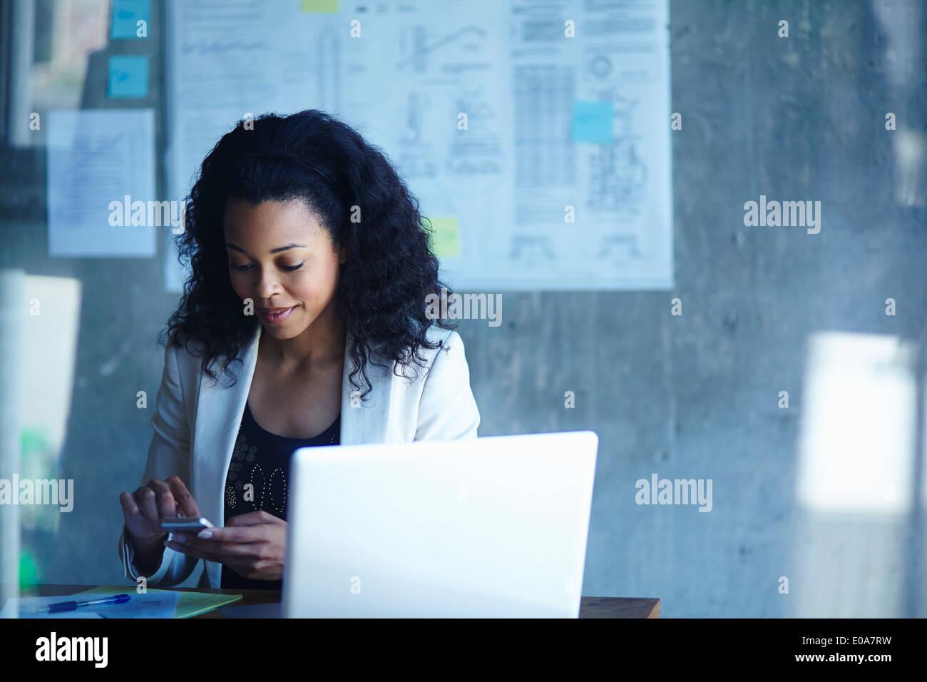 Junge Unternehmerinnen SMS auf Smartphone im Büro Stockbild
