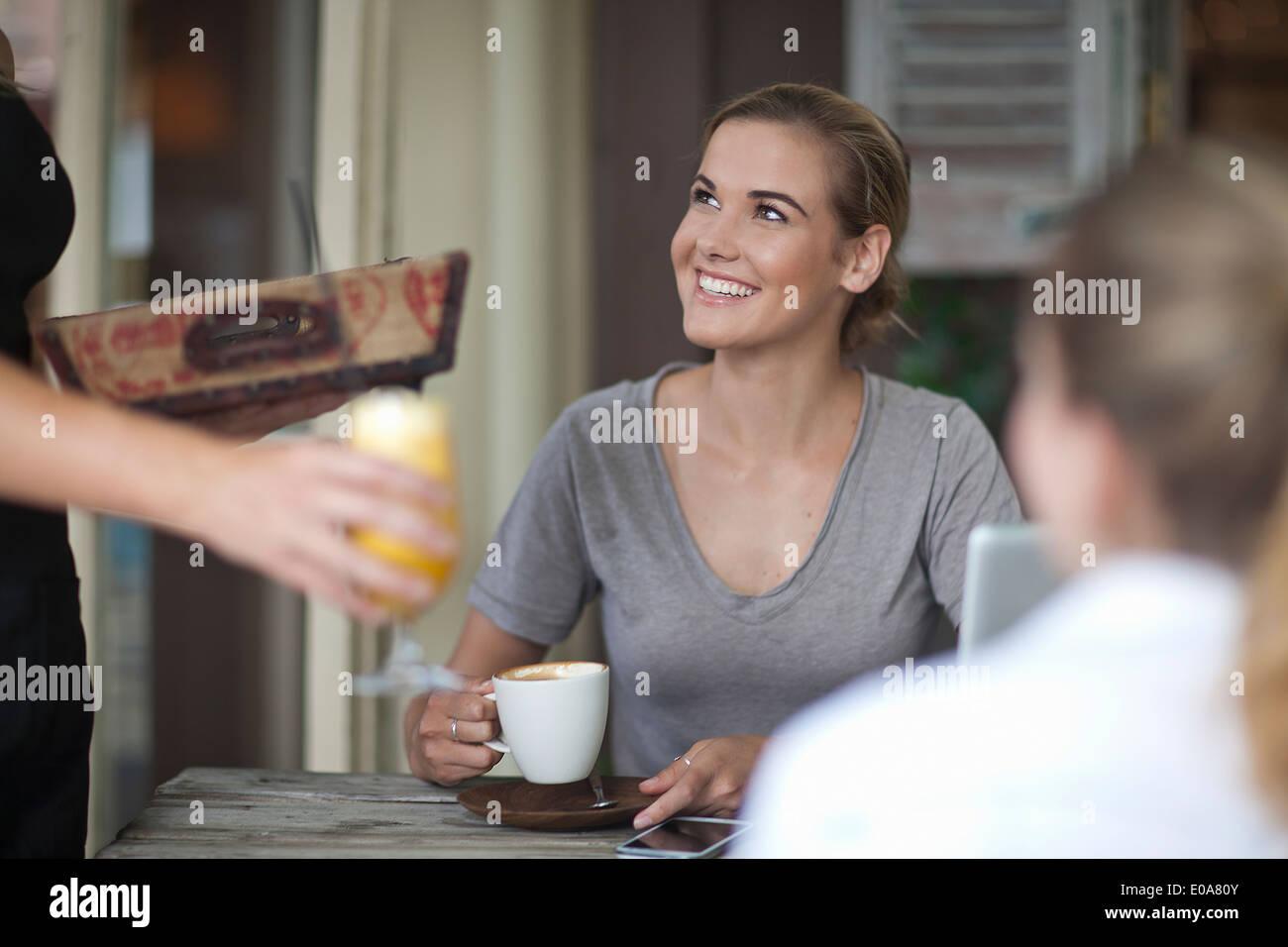 Zwei junge Erwachsene weibliche Freunde Menü im Café bestellen Stockbild