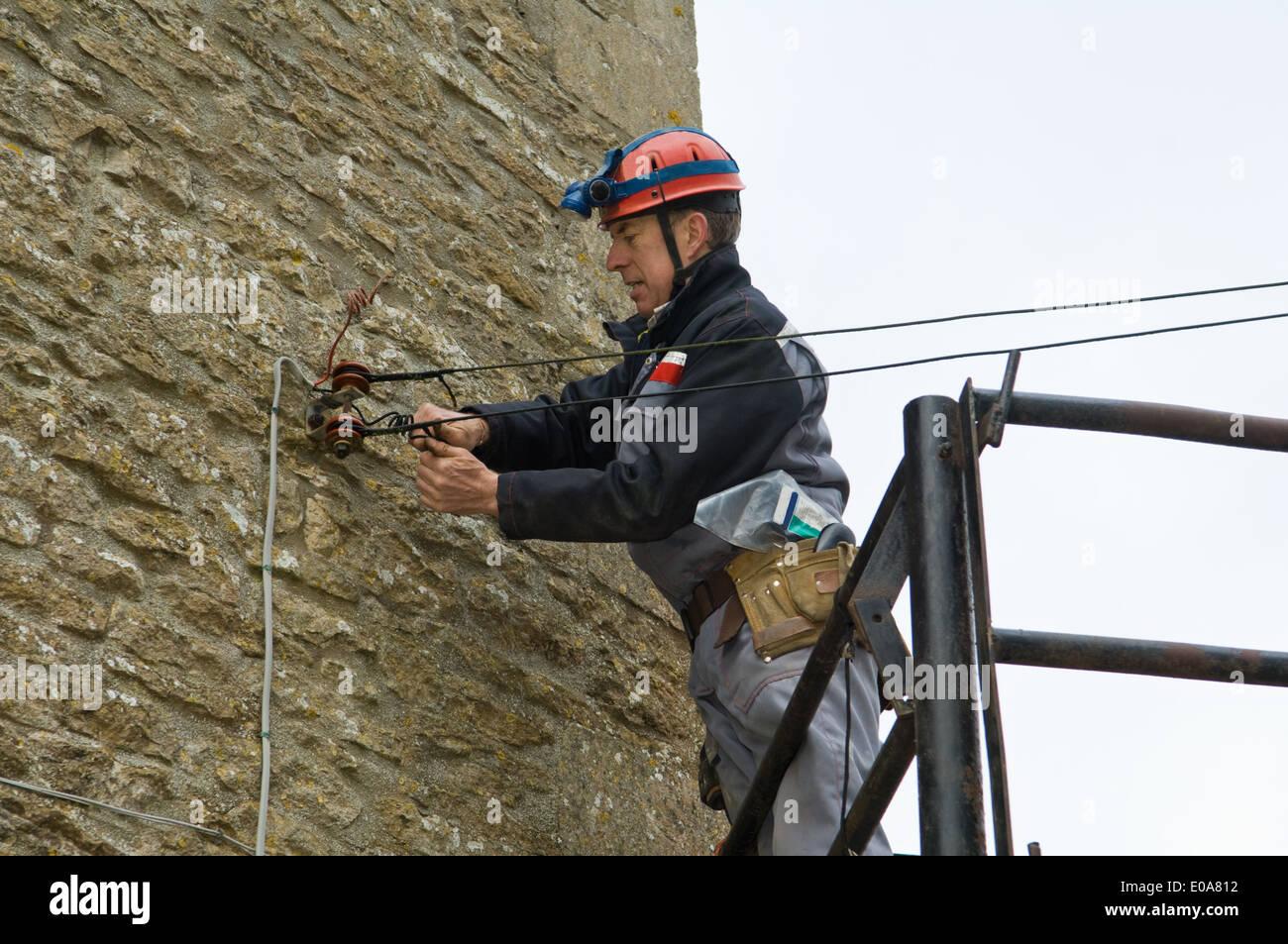 Männliche Elektriker auf Plattform Befestigung Haus Strom liefern Stockbild