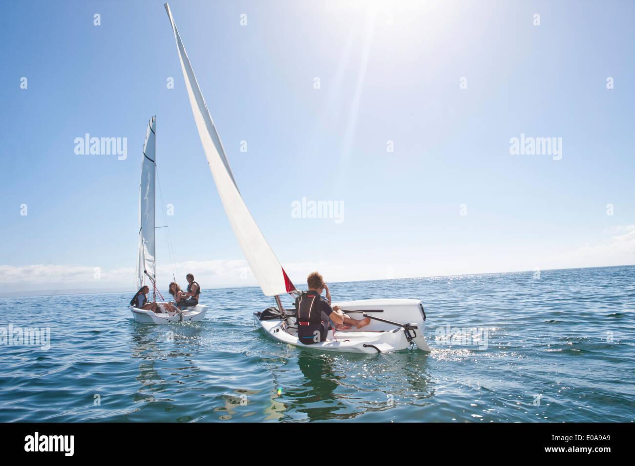 Junge Erwachsene Freunde einander in Segelbooten racing Stockbild