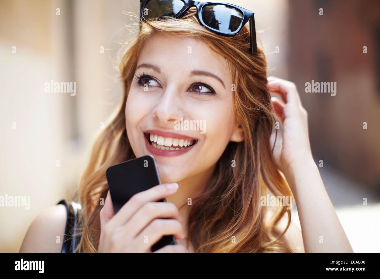 Anspruchsvolle junge Frau mit Smartphone nachschlagen Stockbild